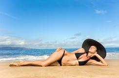 Femme s'exposant au soleil sur la plage photo libre de droits