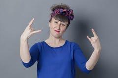 Femme 30s fraîche faisant le geste de main de hard rock pour la satisfaction audacieuse Image libre de droits