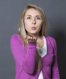 Femme 20s heureuse montrant l'amitié dans les signes boudants et de baisers Images stock