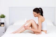 Femme s'inquiétant de ses pattes avec la lotion Photos stock