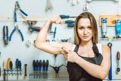 Femme sûre démontrant son biceps dans l'atelier photo stock
