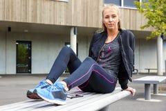 Femme sûre dans la musique de écoute de vêtements de sport sur le banc photos stock