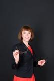 Femme sûre gaie d'affaires se tenant dans la pièce sombre de bureau et regardant l'appareil-photo tenant des verres charmer Image libre de droits