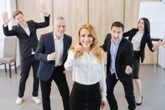 Femme sûre joyeuse se tenant devant ses collègues Photos stock