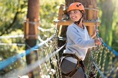 Femme sûre optimiste passant le temps en parc de corde raide Image libre de droits
