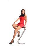 Femme sûre s'asseyant sur des selles et regardant l'appareil-photo photographie stock