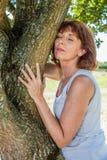 Femme 50s rougeoyante touchant un arbre en harmonie avec la nature Photos stock