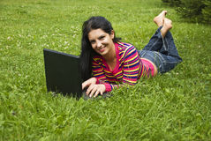 Femme s'étendant dans l'herbe verte et travaillant sur l'ordinateur portatif Photographie stock libre de droits