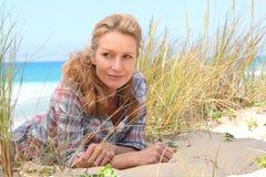 Femme s'étendant sur le sable Photo libre de droits