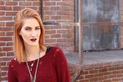 Femme sale de gingembre et un mur de briques Photo de mode image stock