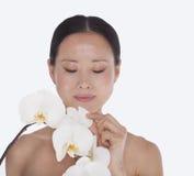 Femme sans chemise sereine regardant vers le bas et touchant un groupe de belles fleurs blanches, tir de studio Images libres de droits
