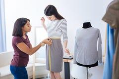 Femme satisfaisante attendant son tailleur pour finir la mesure Image stock