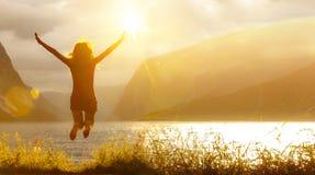Femme sautante heureuse à un lac photos stock