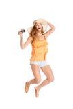Femme sautante tenant un appareil-photo Image libre de droits