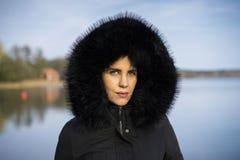 Femme scandinave caucasienne de Moyen Âge se tenant dehors en Suède utilisant la veste et le hoodie noirs sur la tête photographie stock libre de droits