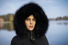 Femme scandinave caucasienne de Moyen Âge se tenant dehors en Suède utilisant la veste et le hoodie noirs sur la tête photo libre de droits