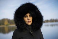 Femme scandinave caucasienne de Moyen Âge se tenant dehors en Suède utilisant la veste et le hoodie noirs sur la tête photographie stock