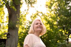 Femme scandinave supérieure dans le jardin d'été entre le sourire d'arbres images stock