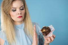 Femme sceptique tenant le petit pain de petit gâteau de chocolat Photo stock