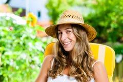 Femme se bronzant dans son jardin sur la chaise longue Photographie stock libre de droits