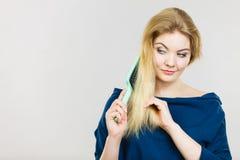 Femme se brossant les longs cheveux avec la brosse Image stock