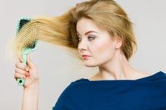 Femme se brossant les longs cheveux avec la brosse images stock