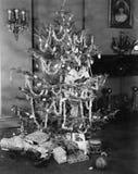 Femme se cachant dans un arbre de Noël décoré (toutes les personnes représentées ne sont pas plus long vivantes et aucun domaine  Image stock