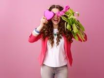 Femme se cachant derrière le bouquet et la boîte en forme de coeur de chocolats Photos libres de droits