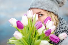 Femme se cachant derrière un bouquet des tulipes photos stock
