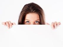 Femme se cachant derrière le panneau d'affichage Photos stock