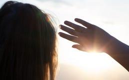 Femme se cachant du soleil avec la main Photo stock