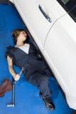 Femme se couchant sur le plancher travaillant à la voiture dans le garage d'automobile photos stock