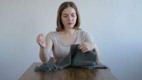 Femme se démêlant le tricotage gris banque de vidéos
