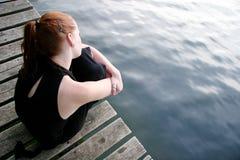 Femme se demandant au lac Photo stock