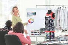 Femme se dirigeant ? la palette de couleurs d'?chantillon tout en discutant quelle couleur pour choisir avec le coll?gue image stock