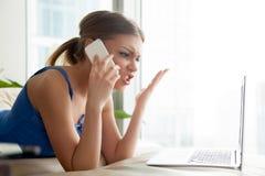 Femme se disputant sur le téléphone portable tout en à l'aide de l'ordinateur portable Images libres de droits