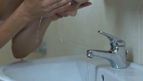 Femme se lavant le visage dans la salle de bains dans le matin, l'eau régénératrice, soins de la peau banque de vidéos