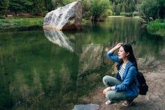 Femme se mettant à genoux en bas de la détente au lac de miroir images stock