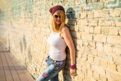 Femme se penchant contre le mur de briques images libres de droits