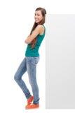 Femme se penchant contre le panneau-réclame blanc Photo stock