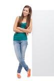 Femme se penchant contre le panneau-réclame blanc Images stock