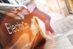 Femme se penchant sur l'entrée principale de la voiture électrique Photographie stock