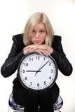Femme se penchant sur l'horloge de mur Image stock