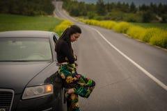 Femme se penchant sur la voiture Photo stock