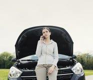 Femme se penchant sur la voiture et appelle un service des réparations de voiture photos stock
