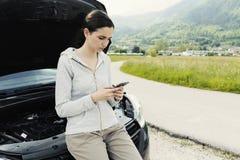 Femme se penchant sur la voiture et appelle un service des réparations de voiture image libre de droits