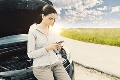 Femme se penchant sur la voiture et appelle un service des réparations de voiture photo stock