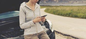 Femme se penchant sur la voiture et appelle un service des réparations de voiture image stock