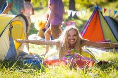 Femme se penchant sur le ballon de plage au terrain de camping Photos libres de droits