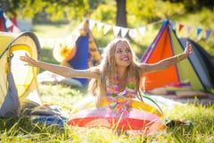 Femme se penchant sur le ballon de plage au terrain de camping Image libre de droits